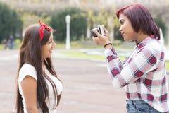 Jeune femme prenant des photos de ses amis en parc Photographie stock