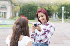 Jeune femme prenant des photos de ses amis en parc Images libres de droits