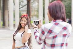 Jeune femme prenant des photos de ses amis en parc Images stock