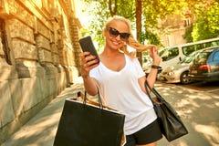 Jeune femme prenant des selfies sur la rue avec des sacs photos libres de droits