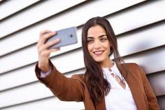 Jeune femme prenant la photographie de selfie avec le smartphone en Ba urbain Photos stock