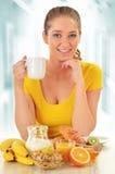 Jeune femme prenant le petit déjeuner photographie stock