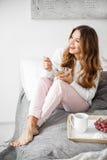 Jeune femme prenant le petit déjeuner dans le lit au matin Photo stock