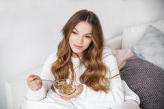 Jeune femme prenant le petit déjeuner dans le lit au matin Photographie stock libre de droits