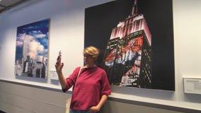 Jeune femme prenant le selfie au fond d'une peinture d'Empire State Building banque de vidéos
