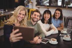 Jeune femme prenant le selfie avec des amis de comprimé au café Photo stock