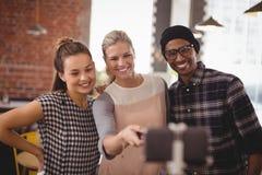 Jeune femme prenant le selfie avec des amis de téléphone portable au café Images stock
