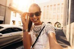 Jeune femme prenant le selfie dans une rue entourée par des bâtiments photos stock