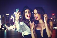 Jeune femme prenant le selfie dedans en centre ville la nuit Photos libres de droits