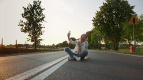 Jeune femme prenant le selfie sur la route Belle jeune dame souriant et posant pour le selfie tout en se reposant sur la route en banque de vidéos