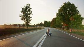 Jeune femme prenant le selfie sur la route Belle jeune dame souriant et posant pour le selfie tout en se reposant sur la route en clips vidéos
