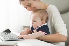 Jeune femme prenant soin de bébé au bureau Photo libre de droits
