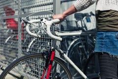 Jeune femme prenant son vélo hors d'un hangar de bicyclette Photo stock