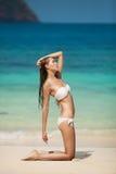 Jeune femme prenant un bain de soleil à la plage tropicale Image stock