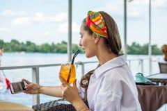 Jeune femme prenant un selfie avec le téléphone portable pour les réseaux et le cocktail sociaux de boissons photographie stock libre de droits
