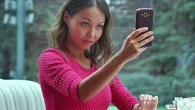 Jeune femme prenant un selfie dans le café banque de vidéos