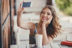 Jeune femme prenant un selfie dans un café Photo libre de droits