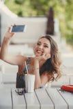 Jeune femme prenant un selfie dans un café Photos libres de droits
