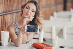 Jeune femme prenant un selfie dans un café Image libre de droits