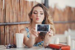 Jeune femme prenant un selfie dans un café Images libres de droits