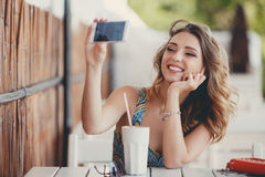 Jeune femme prenant un selfie dans un café Photographie stock libre de droits