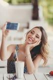 Jeune femme prenant un selfie dans un café Photographie stock