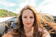 Jeune femme prenant un selfie dans un convertible Photos libres de droits