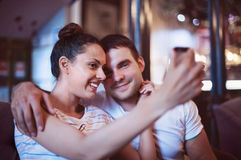 Jeune femme prenant une photo avec son téléphone portable dans un café Photographie stock