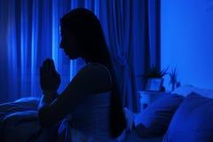 Jeune femme priant dans la chambre noire la nuit photos libres de droits