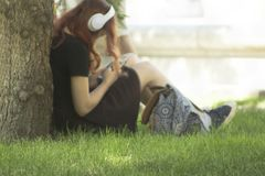 Jeune femme principale rouge Defocused avec les écouteurs et le smartphone blancs dans des mains se reposant sous l'arbre sur une photos stock
