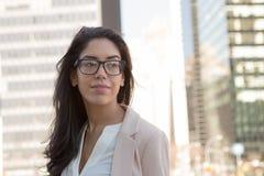 Jeune femme professionnelle latine avec des verres dans la ville Images stock