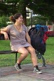 Jeune femme péruvienne sur le banc avec le sac à dos Photo stock