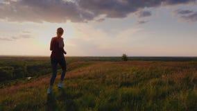 Jeune femme pulsant dans une tache scénique au coucher du soleil Vue arrière 4K ralentissent la vidéo animée banque de vidéos