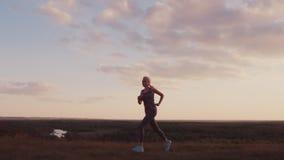 Jeune femme pulsant dans une tache scénique au coucher du soleil Vue de côté clips vidéos