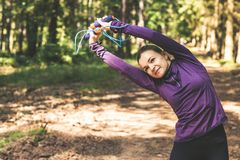 Jeune femme pulsant et faisant des exercices dans la forêt ensoleillée photos libres de droits