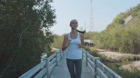 Jeune femme pulsant sur le chemin forestier de palétuviers Steadicam a tiré dans le mouvement lent clips vidéos