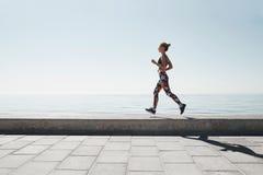 Jeune femme pulsante d'athlète courant au fond de mer Photo stock