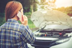 Jeune femme réclamant l'aide avec sa voiture décomposée par t photographie stock libre de droits