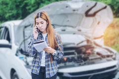 Jeune femme réclamant l'aide avec sa voiture décomposée par t Photo stock