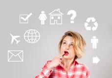 Jeune femme réfléchie avec des icônes de multimédia autour de sa tête Images libres de droits