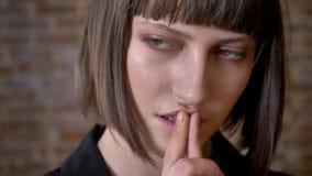 Jeune femme réfléchie avec les yeux verts touchant ses lèvres regardant l'appareil-photo et en longueur, fond de brique banque de vidéos