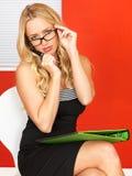 Jeune femme réfléchie d'affaires s'asseyant avec des affaires d'anf de stylo Image stock