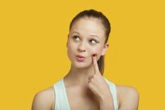 Jeune femme réfléchie regardant en longueur au-dessus du fond jaune Image libre de droits