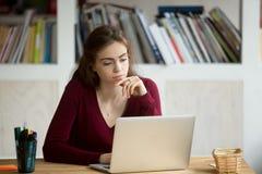 Jeune femme réfléchie regardant l'ordinateur portable, éducation numérique, onl photos libres de droits