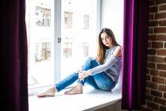 Jeune femme réfléchie s'asseyant sur un filon-couche de fenêtre et regardant dehors Photo libre de droits