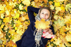 Jeune femme rêvant dans des feuilles d'automne Photographie stock libre de droits