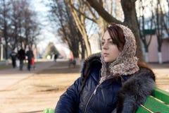 Jeune femme rêvassant sur un banc de parc images stock