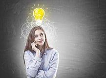 Jeune femme rêveuse dans une chemise bleue, idée image stock