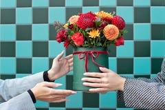 Jeune femme recevant de belles fleurs de pivoine de la femme de la livraison photographie stock libre de droits