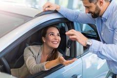 Jeune femme recevant des clés d'un concessionnaire automobile Photos libres de droits